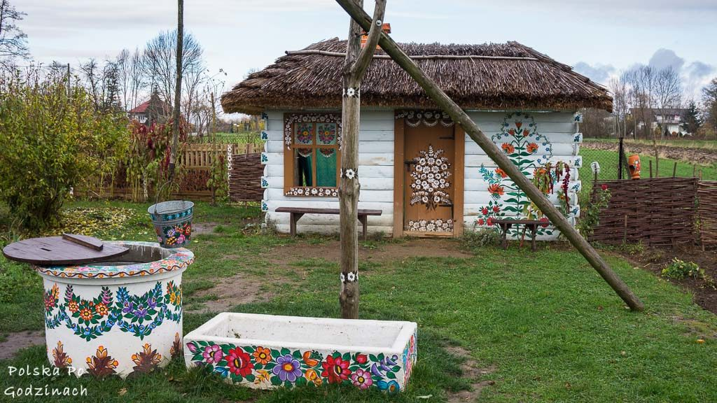 Mała, kolorowa i ukwiecona chatka i studnia w Zalipiu, które jest jedną z atrakcji Małopolski.