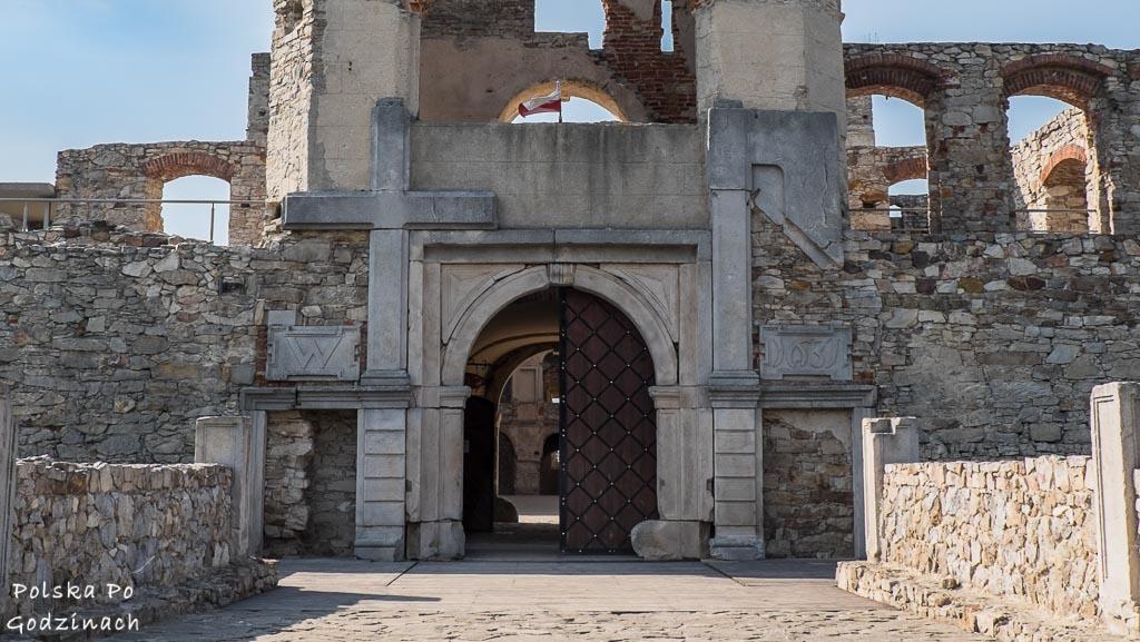 most i brama zamkowa z symbolami krzyża i topora