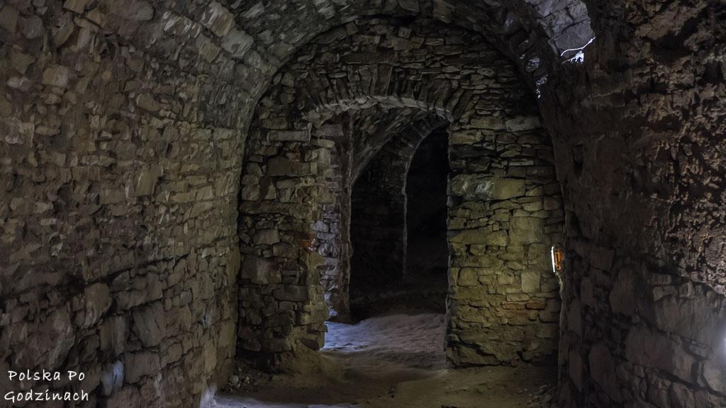 Długi, ciemny korytarz zamkowy.